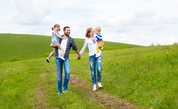愉快的家庭:母亲、父亲、孩子儿子和女儿在夏天 库存图片