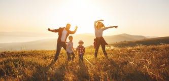 愉快的家庭:母亲、父亲、sunse的孩子儿子和女儿 免版税库存照片