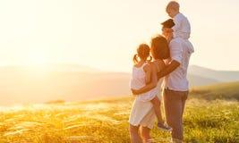 愉快的家庭:母亲、父亲、sunse的孩子儿子和女儿 免版税图库摄影