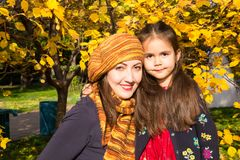 愉快的家庭:母亲和儿童女儿获得乐趣在秋天公园的秋天 拥抱在叶子的年轻母亲和孩子女孩在秋天 免版税库存照片