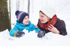 愉快的家庭:母亲和小儿子获得与雪的乐趣在wint 库存图片