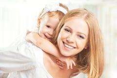 愉快的家庭:笑母亲和小的女儿拥抱和 免版税库存照片