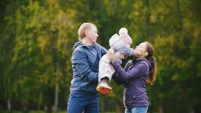 愉快的家庭:走在秋天的父亲、母亲和儿童小女孩停放:使用在草,慢动作 股票录像