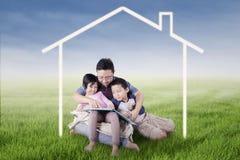愉快的家庭读了书在房子标志下 库存图片