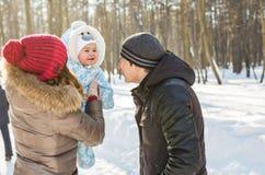 愉快的家庭-母亲、父亲和儿童男孩在一个冬天走 图库摄影