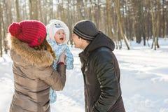 愉快的家庭-母亲、父亲和儿童男孩在一个冬天走 免版税图库摄影