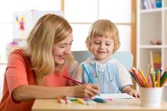 愉快的家庭-母亲和儿子小孩一起绘 对儿童男孩的妇女帮助 图库摄影