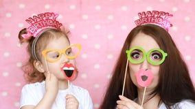 愉快的家庭-母亲和女儿穿戴玻璃和嘴唇和不同的装饰庆祝生日 的treadled 股票视频