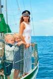 愉快的家庭-母亲,儿子,女儿在船上航行游艇 图库摄影