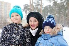 愉快的家庭& x28; 母亲,女儿, son& x29;在降雪期间的姿势 免版税库存图片