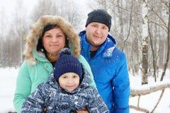愉快的家庭& x28; 母亲,父亲, son& x29;在降雪期间的姿势 库存图片