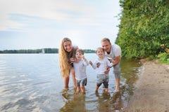 愉快的家庭-父亲,母亲,海滩的两个儿子与他们的脚在水中在日落 免版税库存图片