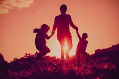 愉快的家庭-生与跳跃从在日落自然的喜悦的儿子和女儿 免版税库存图片