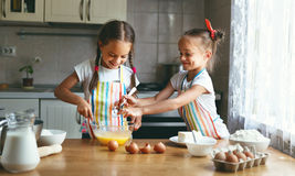 愉快的家庭滑稽的儿童sisrets孪生烘烤在ki的揉的面团 免版税图库摄影