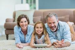 愉快的家庭画象使用数字式片剂的,当说谎在地板上在客厅时 图库摄影