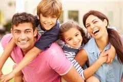 愉快的家庭画象在庭院里在家 免版税库存照片