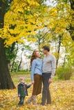 愉快的家庭画象在美丽的秋天公园 库存图片