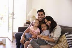 愉快的家庭画象坐沙发在家 库存图片