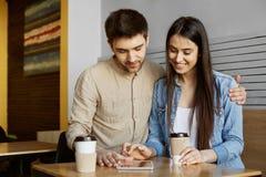 愉快的对画象坐在自助食堂,饮用的茶和寻找在数字式片剂的青年人公寓 免版税图库摄影