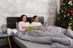 年轻愉快的对阅读书,当在床上在床上时 库存图片
