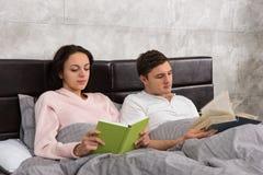 年轻愉快的对阅读书,当在床和wearin上时 库存图片