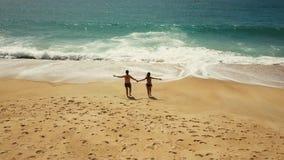愉快的对水的夫妇无忧无虑的赛跑在海滩 葡萄牙的美丽如画的海洋海岸 股票录像