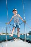 愉快的小在豪华白色游艇的男孩佩带的上尉盖帽在夏日 库存照片