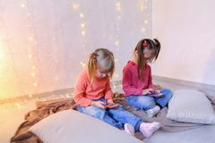 愉快的小女孩为娱乐使用智能手机并且坐  库存图片