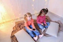愉快的小女孩为娱乐使用智能手机并且坐  免版税库存照片