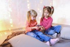 愉快的小女孩为娱乐使用智能手机并且坐  免版税库存图片
