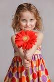 愉快的小女孩产生一朵花某人 免版税图库摄影