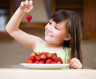 愉快的小女孩吃着草莓 库存照片