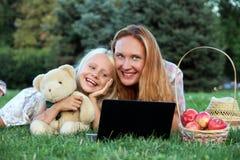 愉快的小女孩和她的母亲有膝上型计算机的 图库摄影