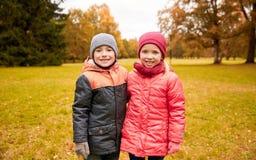愉快的小女孩和男孩在秋天停放 图库摄影
