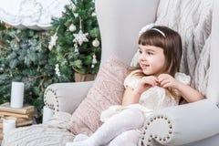 愉快的小女孩在一把轻的米黄家庭椅子舒适地坐 免版税库存照片