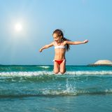 愉快的小女孩在海 免版税库存照片