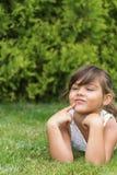 愉快的小女孩在草坪说谎 库存图片