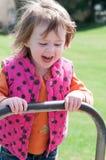愉快的小女孩在跷跷板摇摆 免版税图库摄影