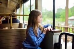愉快的小女孩在主题乐园或游艺集市的坐一列火车 库存图片