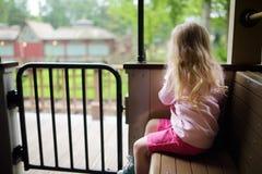 愉快的小女孩在主题乐园或游艺集市的坐一列火车 免版税库存图片