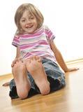 愉快的小女孩坐楼层 免版税库存照片