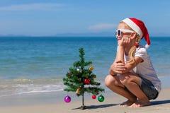 愉快的小女孩坐海滩在天时间 免版税库存图片