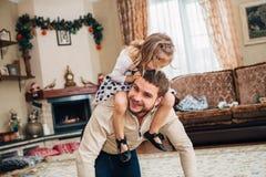 愉快的小女孩坐爸爸` s脖子 免版税库存照片