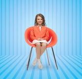 愉快的小女孩坐设计师椅子 库存图片