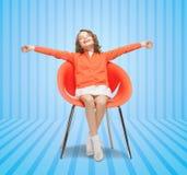 愉快的小女孩坐设计师椅子 免版税库存照片