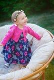 愉快的小女孩坐长沙发和微笑 免版税图库摄影