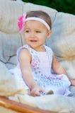 愉快的小女孩坐长沙发和微笑 图库摄影
