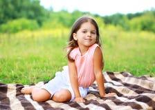 愉快的小女孩夏天画象坐格子花呢披肩 免版税库存图片