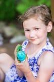 愉快的小女孩姿势用被绘的复活节彩蛋 库存图片