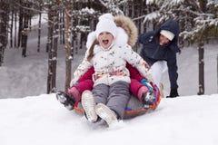 愉快的小女孩尖叫与欢欣,滚动与雪小山 库存图片